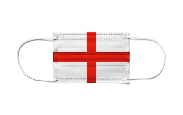 使い捨てサージカルマスクにイギリスの旗。分離された白い背景