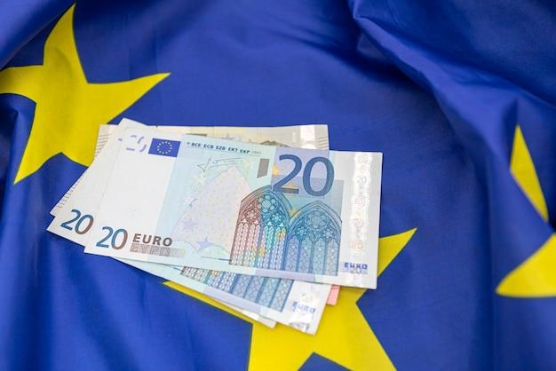 欧州連合euの旗と上部にいくつかのお金のユーロ、