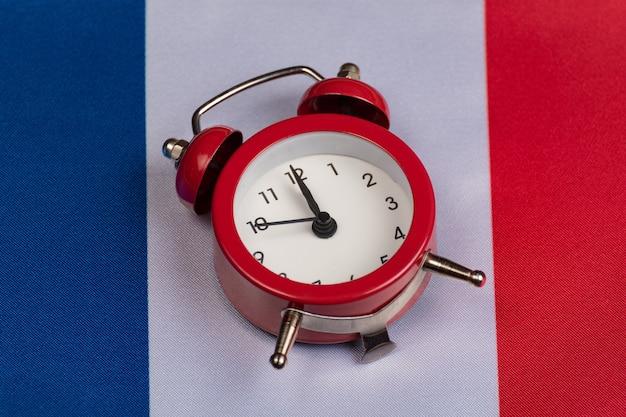 Флаг франции и старинный будильник, крупным планом. время учить французский