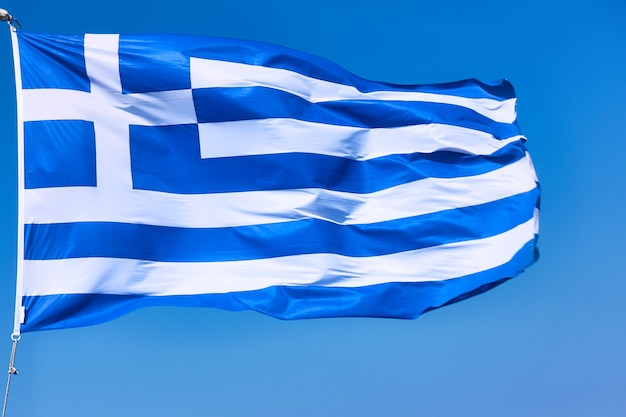 그리스 클로즈업의 국기입니다. 푸른 하늘을 향한 그리스 국기를 흔들다