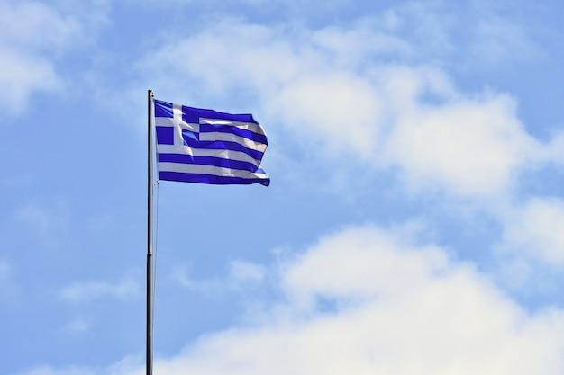 Флаг греции летающий в ветру и голубое небо. летний фон для путешествий и праздников. греция крит.