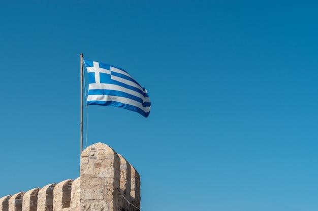 青い空を背景に旗竿にギリシャの旗