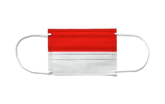 使い捨てサージカルマスクにインドネシアの旗。分離された白い背景