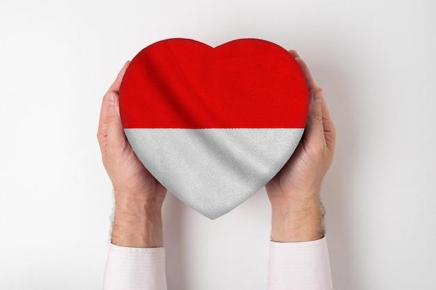 Флаг индонезии на коробке в форме сердца в мужских руках. белый фон