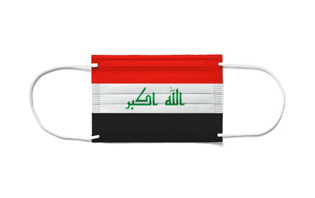 使い捨てのサージカルマスクにイラクの旗。分離された白い背景