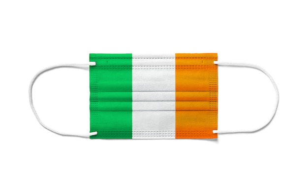 使い捨てサージカルマスクにアイルランドの旗。分離された白い背景