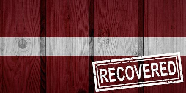 Флаг латвии, которая выжила или оправилась от инфекций, вызванных эпидемией коронавируса или коронавируса. флаг гранж с печатью восстановлено
