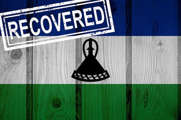 Флаг лесото, который выжил или оправился от инфекций, вызванных эпидемией коронавируса или коронавируса. флаг гранж с печатью восстановлено