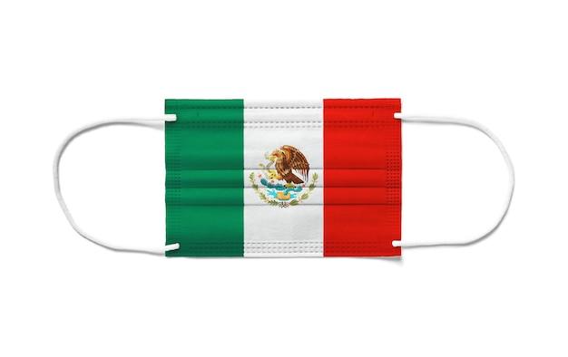 使い捨てサージカルマスクにメキシコの旗。分離された白い背景