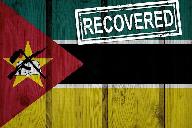 Флаг мозамбика, который выжил или оправился от инфекций, вызванных эпидемией коронавируса или коронавируса. флаг гранж с печатью восстановлено