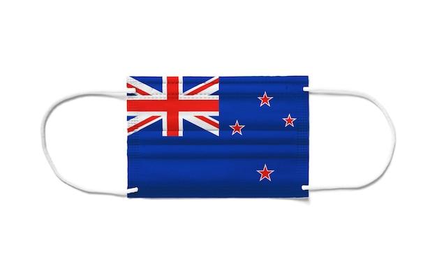 使い捨てサージカルマスクにニュージーランドの旗。分離された白い背景