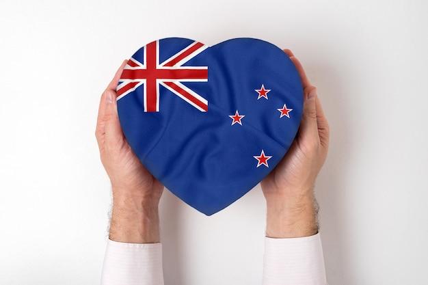 Флаг новой зеландии на коробке в форме сердца в мужских руках. белый
