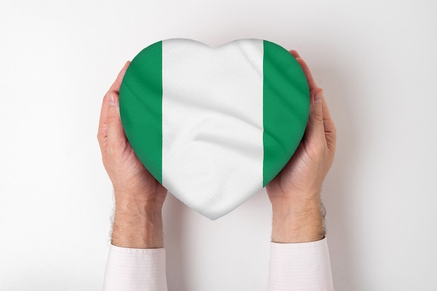 Флаг нигерии на коробке в форме сердца в мужских руках. белый фон