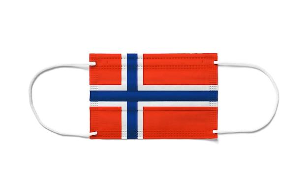 使い捨てサージカルマスクにノルウェーの旗。分離された白い背景
