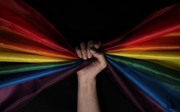 プライドの旗。 lgbtqの旗と手。レズビアンゲイバイセックストランスジェンダークィアまたは同性愛プライドレインボーフラッグ。黒の背景。