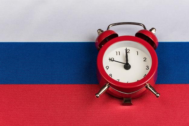 Флаг российской федерации и старинный будильник крупным планом.