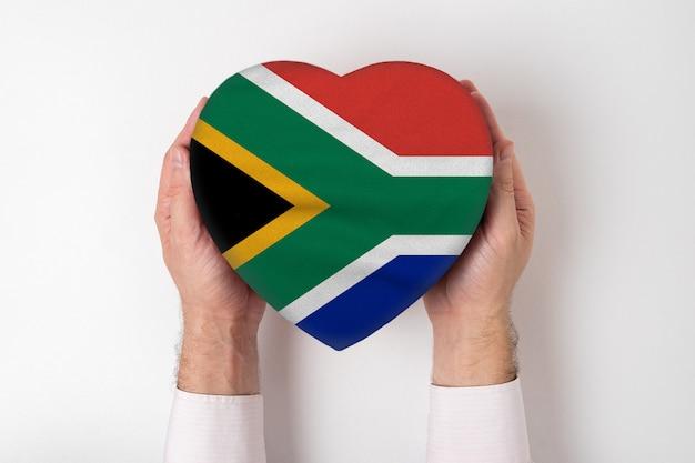 Флаг южной африки на коробке в форме сердца в мужских руках.