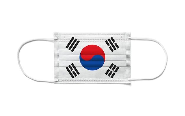 使い捨てサージカルマスクに韓国の旗。分離された白い背景