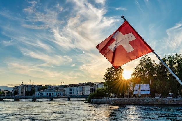 Флаг швейцарии на переднем плане на закате в городе женева, швейцария. озеро леман.
