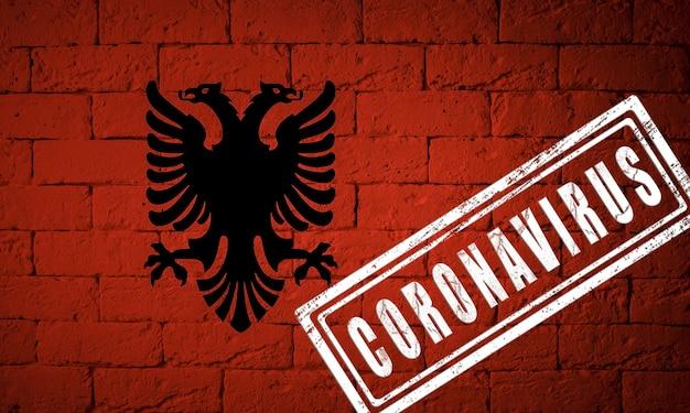 オリジナルのプロポーションを持つアルバニアの旗。コロナウイルスの刻印。レンガの壁のテクスチャ。コロナウイルスの概念。 covid-19または2019-ncovパンデミックの危機に瀕しています。
