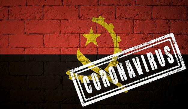 コロナウイルスコロナウイルスの概念が刻印されたレンガの壁のテクスチャにアンゴラの旗