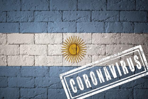 オリジナルのプロポーションを持つアルゼンチンの旗。コロナウイルスの刻印。レンガの壁のテクスチャ。コロナウイルスの概念。 covid-19または2019-ncovパンデミックの危機に瀕しています。