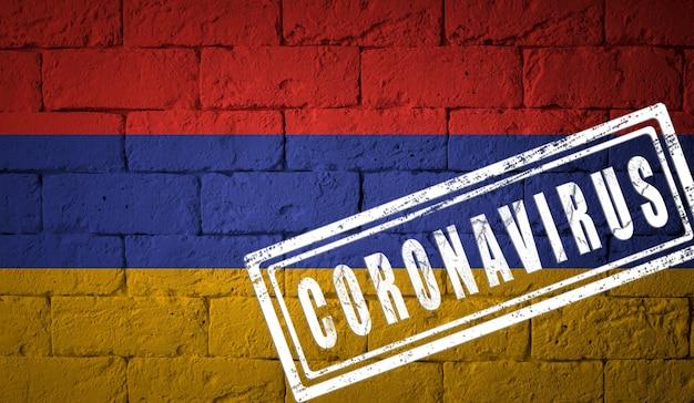 オリジナルのプロポーションを持つアルメニアの旗。コロナウイルスの刻印。レンガの壁のテクスチャ。コロナウイルスの概念。 covid-19または2019-ncovパンデミックの危機に瀕しています。