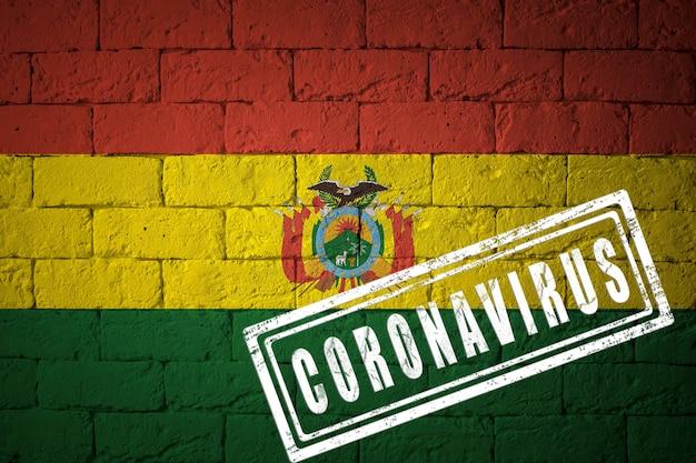 オリジナルのプロポーションを持つボリビアの旗。コロナウイルスの刻印。レンガの壁のテクスチャ。コロナウイルスの概念。 covid-19または2019-ncovパンデミックの危機に瀕しています。