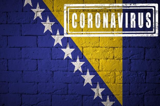 オリジナルのプロポーションを持つボスニア・ヘルツェゴビナの旗。コロナウイルスの刻印。レンガの壁のテクスチャ。コロナウイルスの概念。 covid-19または2019-ncovパンデミックの危機に瀕しています。