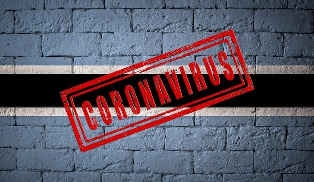 コロナウイルスコロナウイルスの概念が刻印されたレンガの壁のテクスチャにボツワナの旗