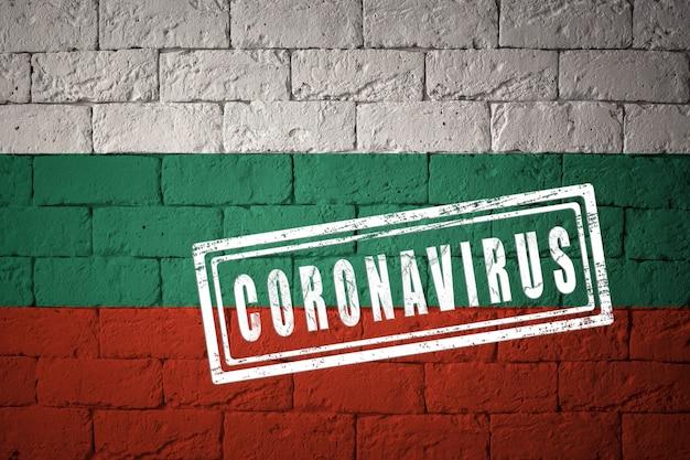 オリジナルのプロポーションを持つブルガリアの旗。コロナウイルスの刻印。レンガの壁のテクスチャ。コロナウイルスの概念。 covid-19または2019-ncovパンデミックの危機に瀕しています。