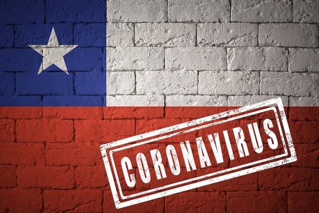 コロナウイルスコロナウイルスの概念が刻印されたレンガの壁のテクスチャにチリの旗