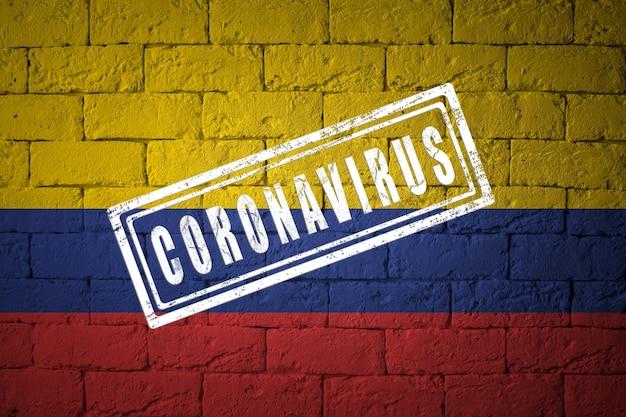 オリジナルのプロポーションを持つコロンビアの旗。コロナウイルスの刻印。レンガの壁のテクスチャ。コロナウイルスの概念。 covid-19または2019-ncovパンデミックの危機に瀕しています。