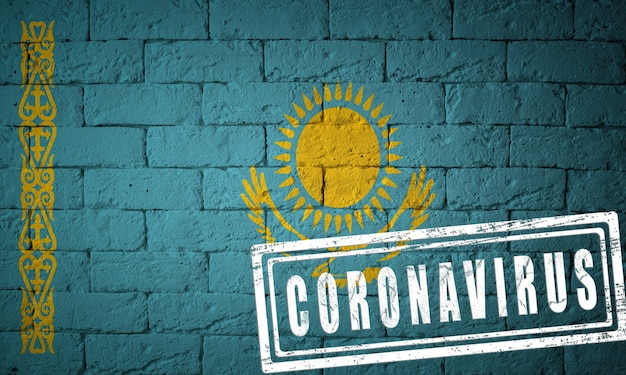 Флаг казахстана с оригинальными пропорциями. штамп коронавируса. текстура кирпичной стены. концепция вируса короны. на грани пандемии covid-19 или 2019-ncov.