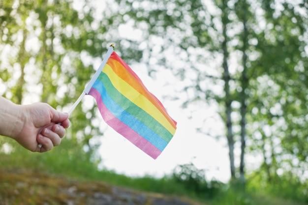 잔디와 나무의 배경에 있는 lgbt 커뮤니티의 깃발, 여성의 손에 든 깃발