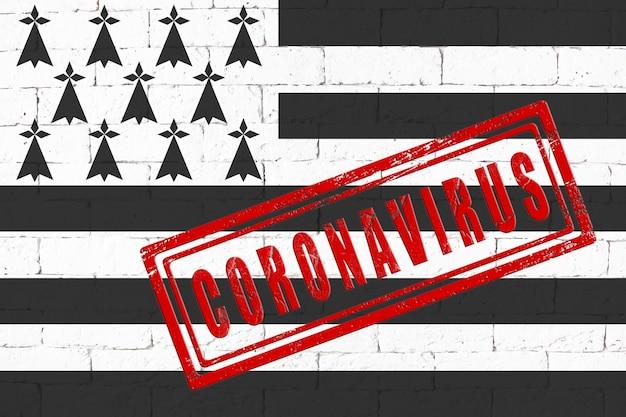 スタンプコロナウイルスで汚れたレンガの壁の背景に描かれたブルターニュ地方の旗