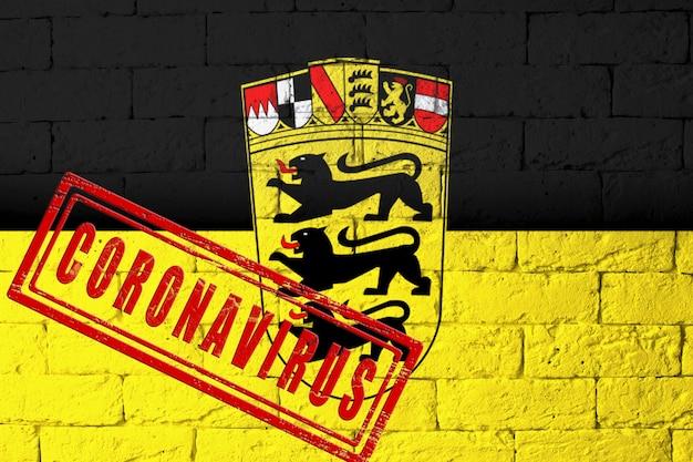 元の比率でドイツのバーデン・ヴュルテンベルク州の地域の旗。コロナウイルスの刻印。レンガの壁のテクスチャ。コロナウイルスの概念。 covid-19または2019-ncovパンデミックの危機に瀕しています。