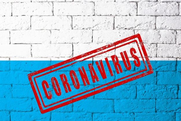 元の比率でドイツバイエルンの地域の旗。コロナウイルスの刻印。レンガの壁のテクスチャ。コロナウイルスの概念。 covid-19または2019-ncovパンデミックの危機に瀕しています。