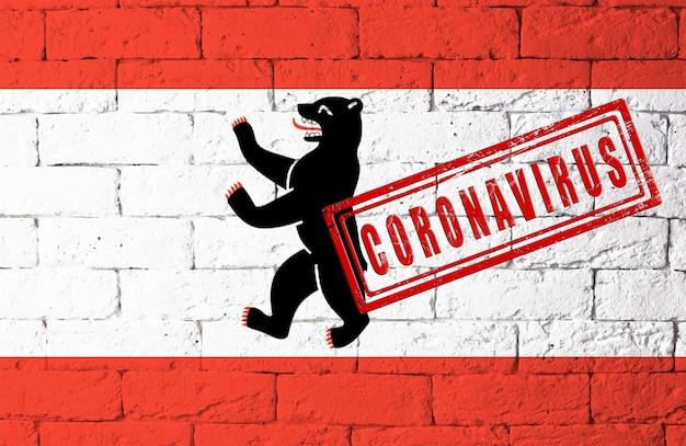 オリジナルのプロポーションを持つドイツベルリンの地域の旗。コロナウイルスの刻印。レンガの壁のテクスチャ。コロナウイルスの概念。 covid-19または2019-ncovパンデミックの危機に瀕しています。
