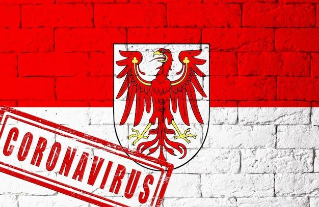 オリジナルのプロポーションを持つドイツのブランデンブルク地方の旗。コロナウイルスの刻印。レンガの壁のテクスチャ。コロナウイルスの概念。 covid-19または2019-ncovパンデミックの危機に瀕しています。