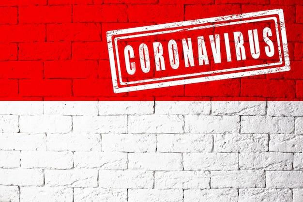 オリジナルのプロポーションを持つドイツヘッセンの地域の旗。コロナウイルスの刻印。レンガの壁のテクスチャ。コロナウイルスの概念。 covid-19または2019-ncovパンデミックの危機に瀕しています。