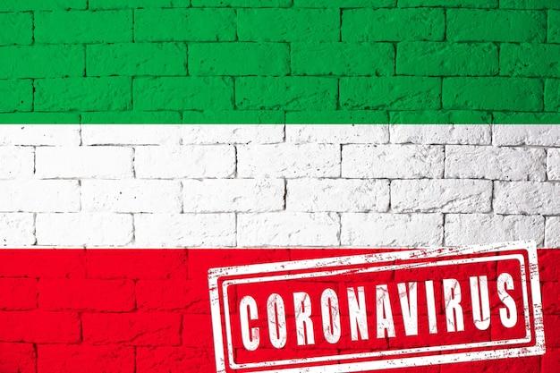 ドイツのノルトライン地方の旗-元の比率で。コロナウイルスの刻印。レンガの壁のテクスチャ。コロナウイルスの概念。 covid-19または2019-ncovパンデミックの危機に瀕しています。