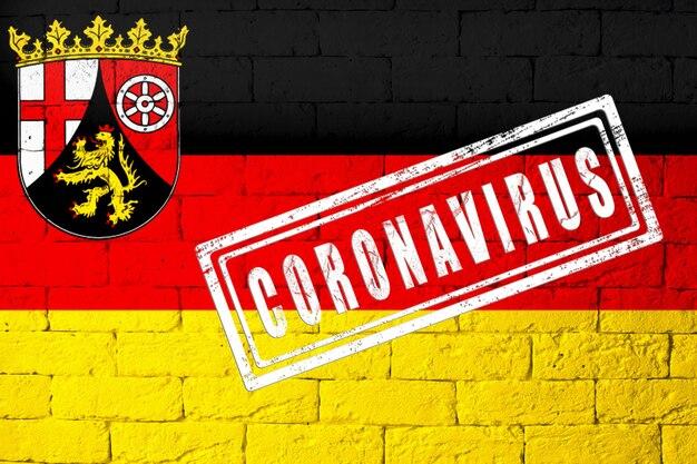 元の比率でドイツのラインラントプファルツ州の地域の旗。コロナウイルスの刻印。レンガの壁のテクスチャ。コロナウイルスの概念。 covid-19または2019-ncovパンデミックの危機に瀕しています。