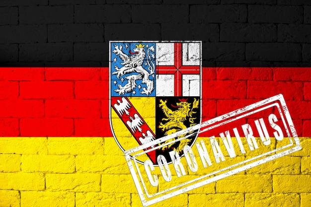 オリジナルのプロポーションを持つドイツザールラント地方の旗。コロナウイルスの刻印。レンガの壁のテクスチャ。コロナウイルスの概念。 covid-19または2019-ncovパンデミックの危機に瀕しています。