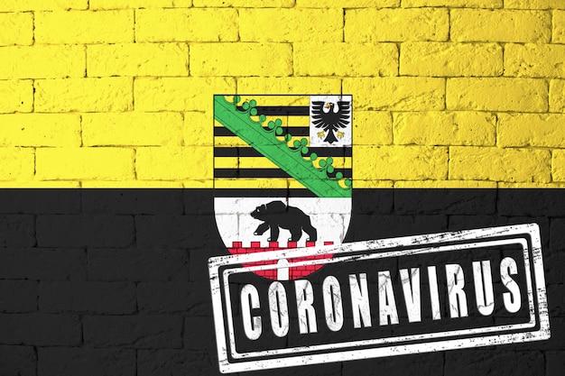 ドイツザクセンアンハルト州の地域の旗。元の比率で。コロナウイルスの刻印。レンガの壁のテクスチャ。コロナウイルスの概念。 covid-19または2019-ncovパンデミックの危機に瀕しています。