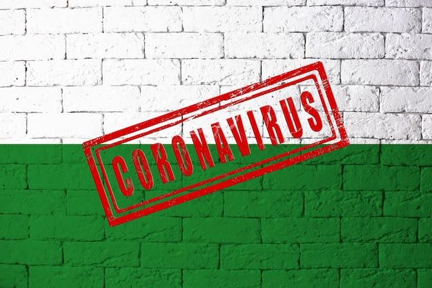 元の比率でドイツザクセン州の地域の旗。コロナウイルスの刻印。レンガの壁のテクスチャ。コロナウイルスの概念。 covid-19または2019-ncovパンデミックの危機に瀕しています。