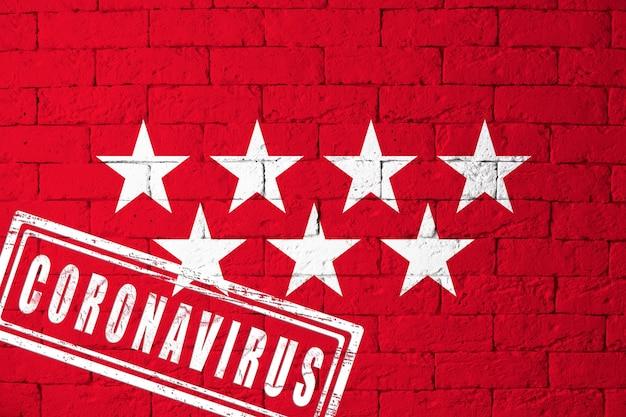 元の比率でスペインマドリードの地域またはコミュニティの旗。コロナウイルスの刻印。レンガの壁のテクスチャ。コロナウイルスの概念。 covid-19または2019-ncovパンデミックの危機に瀕しています。