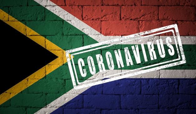オリジナルのプロポーションを持つ南アフリカの旗。コロナウイルスの刻印。レンガの壁のテクスチャ。コロナウイルスの概念。 covid-19または2019-ncovパンデミックの危機に瀕しています。