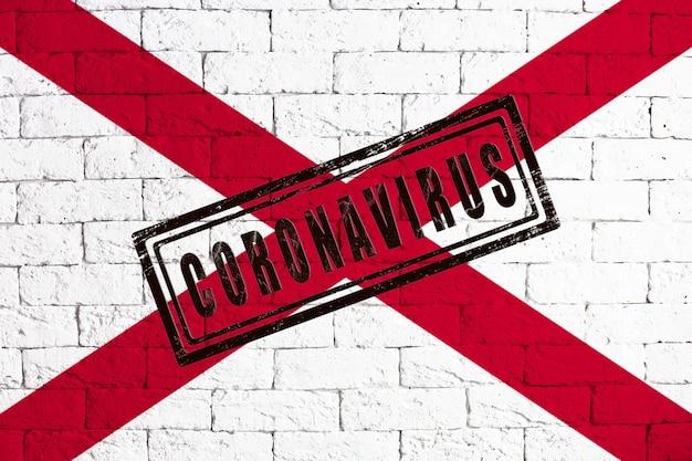 スタンプコロナウイルスで汚れたレンガの壁の背景に描かれたアラバマ州の旗