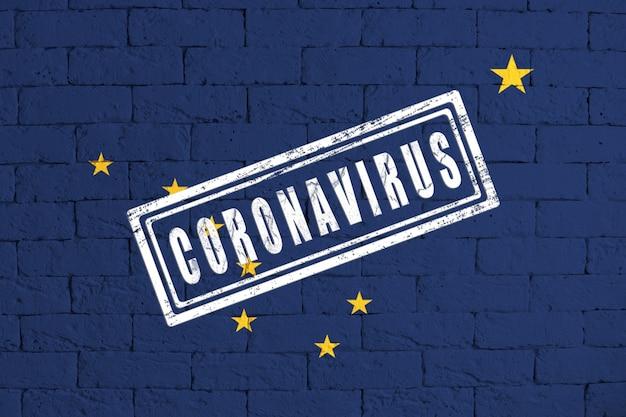 スタンプコロナウイルスで汚れたレンガの壁の背景に描かれたアラスカ州の旗